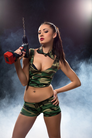 provocative women: Concept photo. Seductive brunette armed with drill