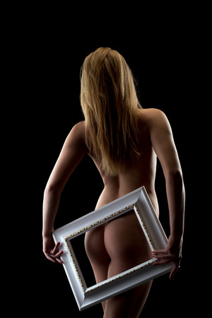 Rear view of naked girl put frame to her ass, isolated on black photo