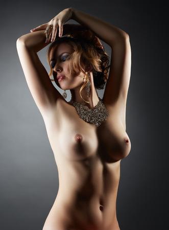 Portrait of beautiful nude model touts jewelry, on gray backdrop