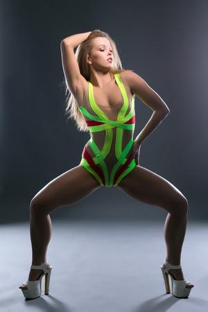 Sexy go-go dancer posing at camera in UV light photo