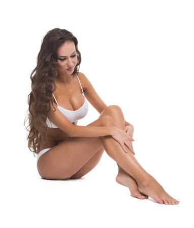 smooth skin: Concept of hair removal. Pretty woman runs her hand over smooth skin of feet