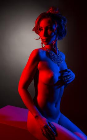 beaux seins: Image de sensuelle nue modèle pose à la lumière rouge et bleu