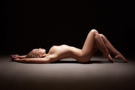 Профиль довольно Обнаженная девушка, лежа на полу в студии