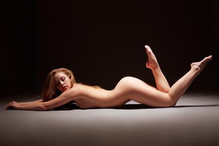 fille nue sexy: Image de attrayante jeune fille nue couchée posant en studio