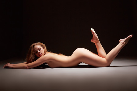 sexy nude girl: Image of attractive naked girl posing lying in studio Stock Photo