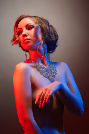 nude model: Pretty nude model advertises jewelry, in red and blue lights Stock Photo