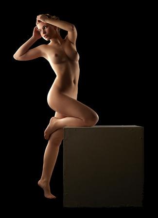 femme noire nue: Nu fille mince posant appuyant sur cube, isol� sur fond noir