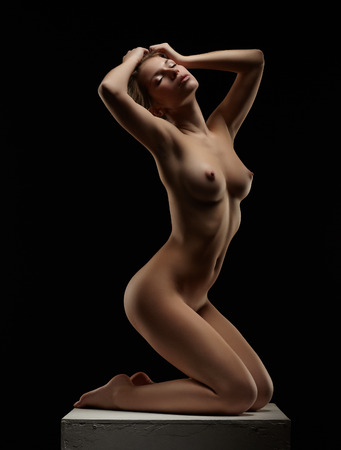 Studio shot of languid nude woman posing on cube, isolated over black background