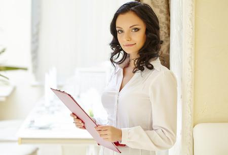 Friendly smiling restaurant hostess posing at camera Stockfoto