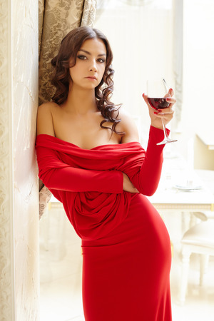 erotic dress: Brunette posing in sexy red dress with glass of wine
