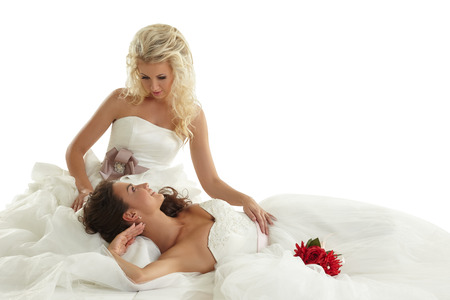 Concept of lesbian wedding. Two alluring brides posing in studio photo