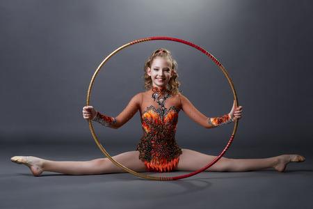 Happy flexible gymnast posing with hoop, on grey background Stock Photo