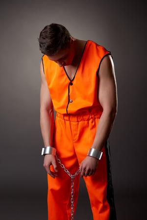 bowed head: Studio shot of prisoner bowed his head, on grey background