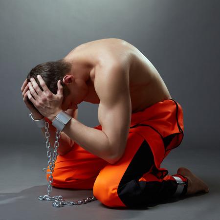 preso: Concepto de prisión. Prisionero agarró la cabeza, sobre fondo gris Foto de archivo