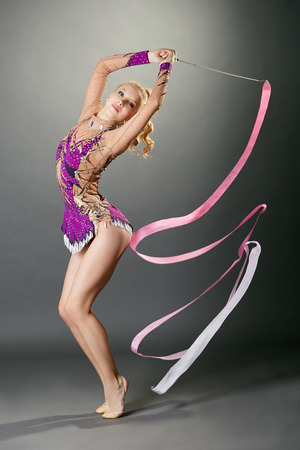 rhythmic gymnastics: Tiro del estudio de baile gimnasta curvado con la cinta, sobre fondo gris Foto de archivo