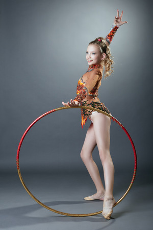 young gymnast: Free callisthenics. Cute young gymnast posing with hoop