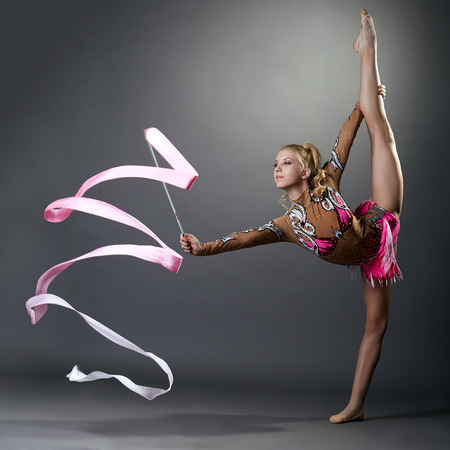 Rhythmic gymnast doing vertical split with ribbon, on grey background