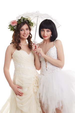 Beautiful brides posing at camera. Concept of double wedding Stock Photo
