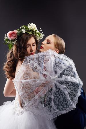 lesbianas: Amigas homosexuales encantadoras que presentan en trajes de boda Foto de archivo