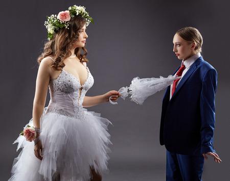 boda gay: El matrimonio gay. Novia atractiva que asoma novio con paraguas, sobre fondo gris