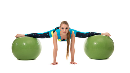 stretched out: Amazing girl stretched out on two fitness balls, isolated over white backdrop Stock Photo