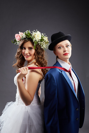 Beautiful lesbian couple in wedding outfits, on gray background