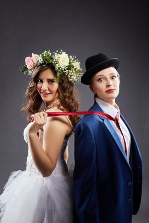 heirat: Schönes lesbisches Paar in der Hochzeits-Outfits, auf grauem Hintergrund Lizenzfreie Bilder