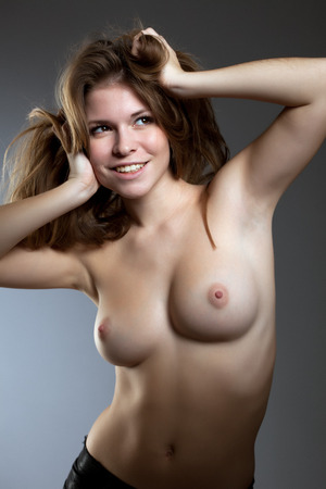 topless brunette: Cute smiling girl posing with naked breasts, close-up