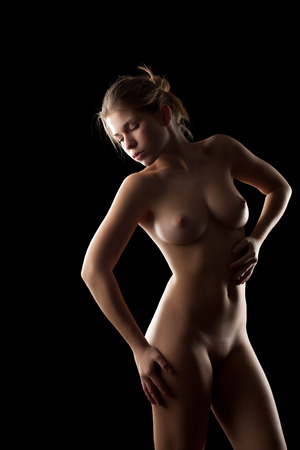 topless brunette: Image of lovely young girl posing nude, isolated on black Stock Photo