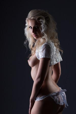 Studio photo of sexy nude bride posing at camera, on grey background