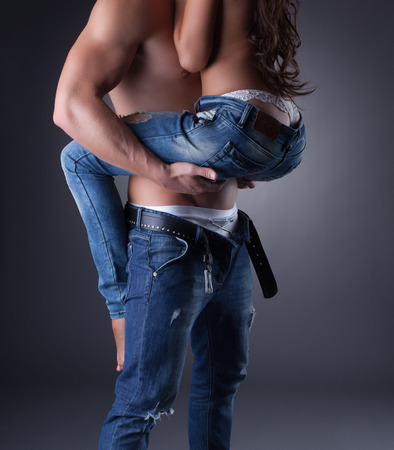 erotic couple: Passionate embrace of sexy models in jeans, close-up