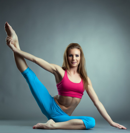 acrobatic: Smiling fitness trainer posing at camera in studio, on gray backdrop