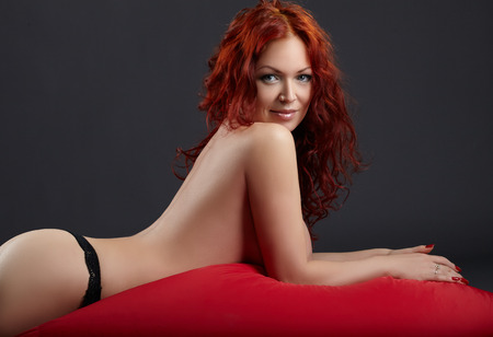 Topless redhead woman posing lying in studio, on gray background