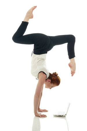 handstand: Concept of multitasking. Girl doing handstand with laptop