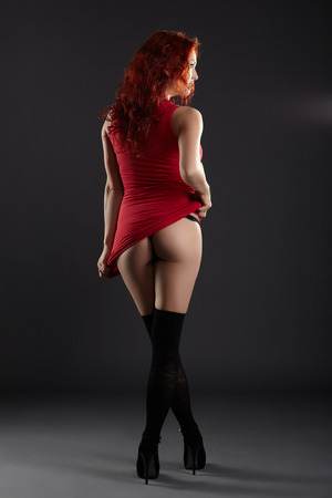 nude ass: Hot red-haired woman bared her ass, on gray background Stock Photo