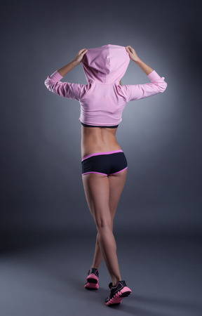 sexy ass: Rear view of sexy female athlete with elastic ass, on grey backdrop