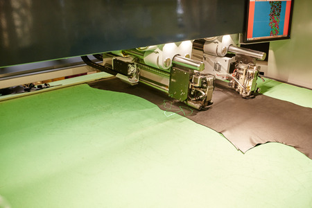 Image of automatic machine cuts leather with laser marking photo
