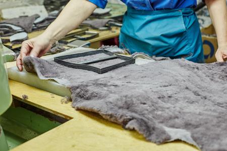 footwear: Image of worker puts templet on pelt. Footwear production