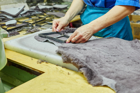 insoles: Production of fur insoles. Worker uses template, close-up