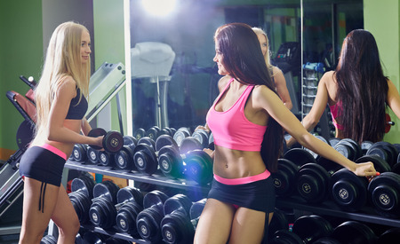 seductive girls: Seductive girls while training with dumbbells in gym