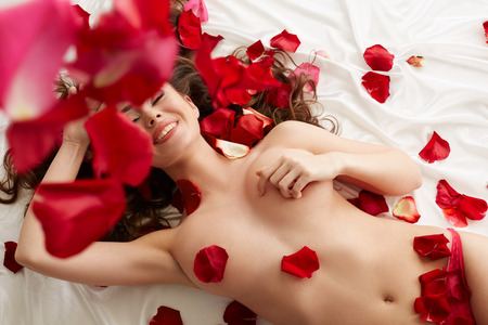 nude brunette: Image of happy naked model lying in bed with rose petals Stock Photo