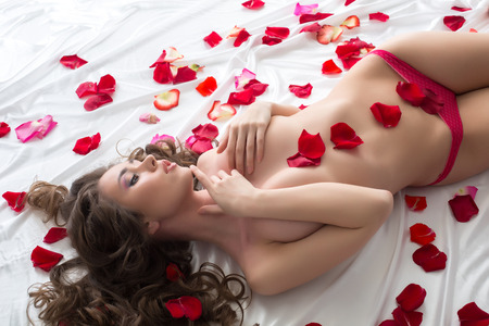 sexy topless women: Image of fascinating topless girl lying with rose petals Stock Photo