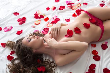 mujer sexy desnuda: Imagen de la fascinante chica en topless tumbada con p�talos de rosa
