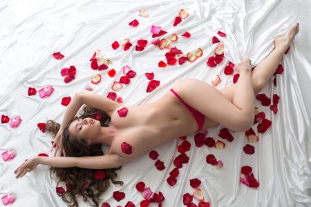 naked young women: Вид сверху заманчивым женщина позирует в постели с лепестками Фото со стока