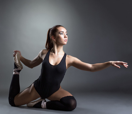 gaiters: Image of inspired ballerina posing in studio, on gray background Stock Photo