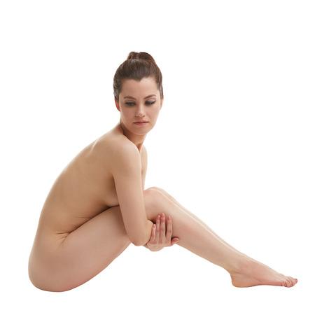 mujeres desnudas: Mujer desnuda atractiva que presenta abraz� las piernas, aislado en blanco Foto de archivo