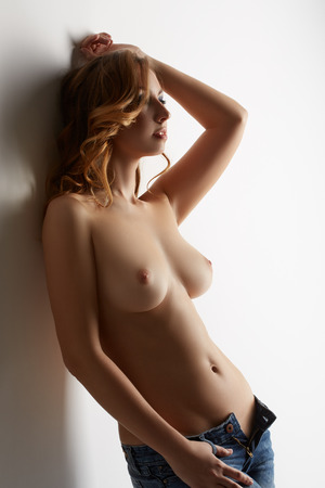 cuerpos desnudos: Modelo en topless seductora posando en jeans, sobre fondo gris