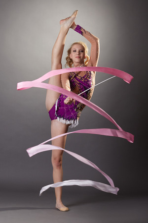 Studio shot of flexible young gymnast dancing with ribbon Фото со стока