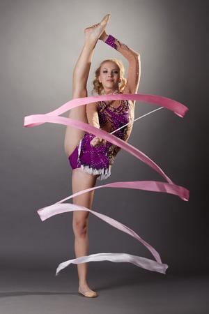 gymnastics equipment: Studio shot of flexible young gymnast dancing with ribbon Stock Photo