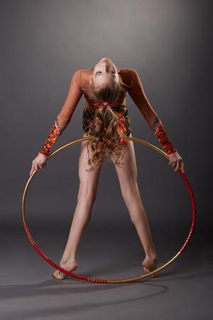 gymnastique: Petite gymnaste mignon joue avec cerceau, sur fond gris